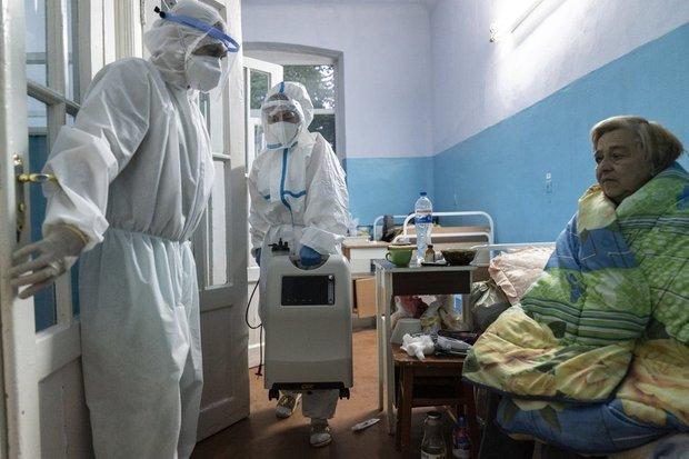 Медсестра несе медичне обладнання, аби допомогти пацієнтці з підозрою на COVID-19 –Чернівці, травень 2020 / Фото: AP